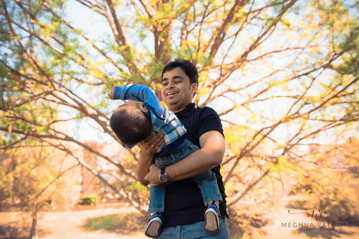 dad holding his kid in the arms and playing with him - outdoor professional photographer
