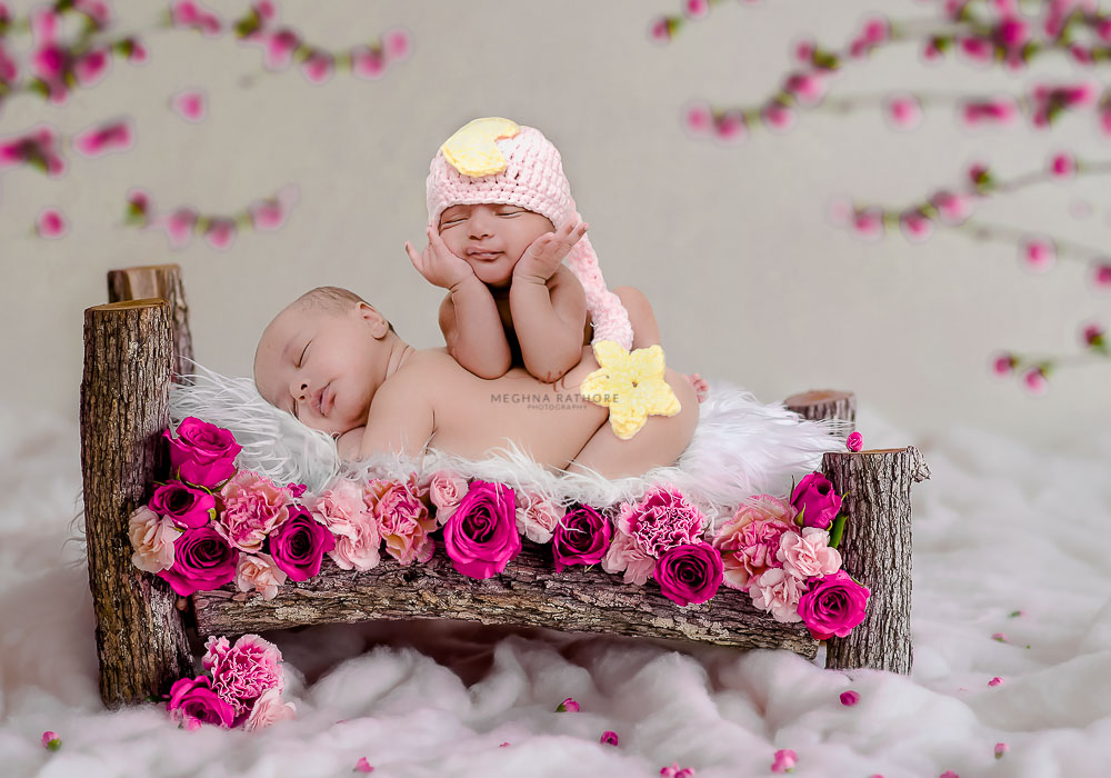 meghna rathore photography twin photo shoot both babies lying on a log bed and one baby is sleeping on another baby