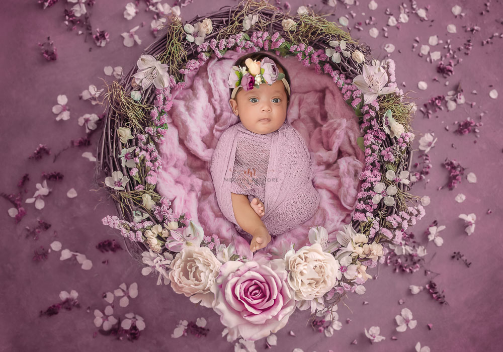 meghna rathore photography baby photo shoot gurgaon baby lying in a basket wrapped in purple color cloth