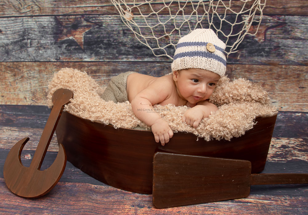 meghna rathore photography baby lying in a small boat and looking curiously