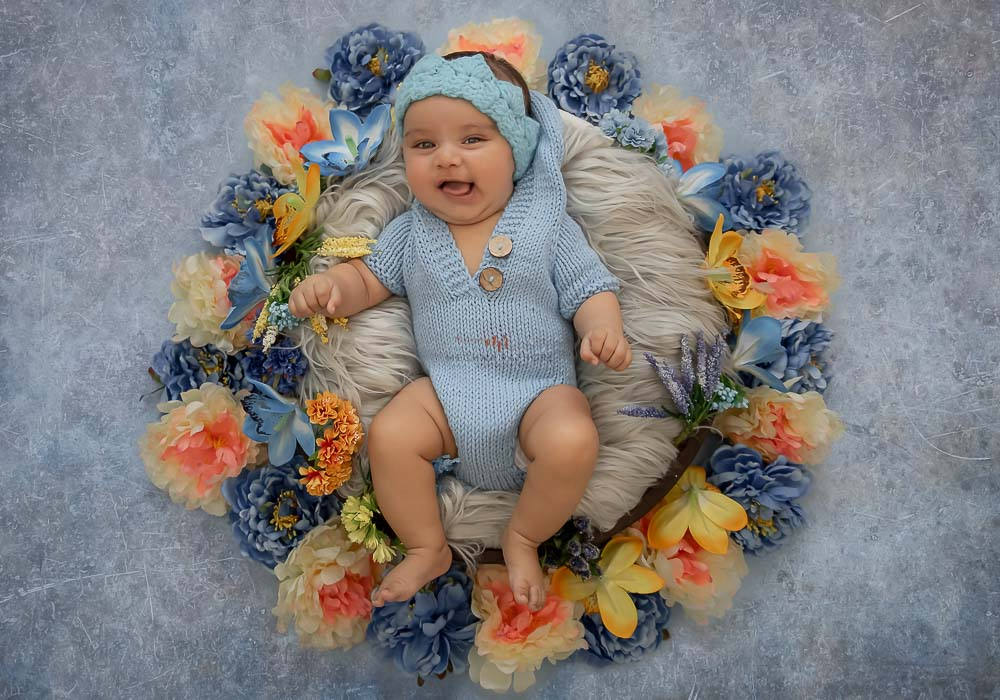 meghna rathore photography baby photo shoot delhi baby lying in a basket with flower decoration and blue backdrop