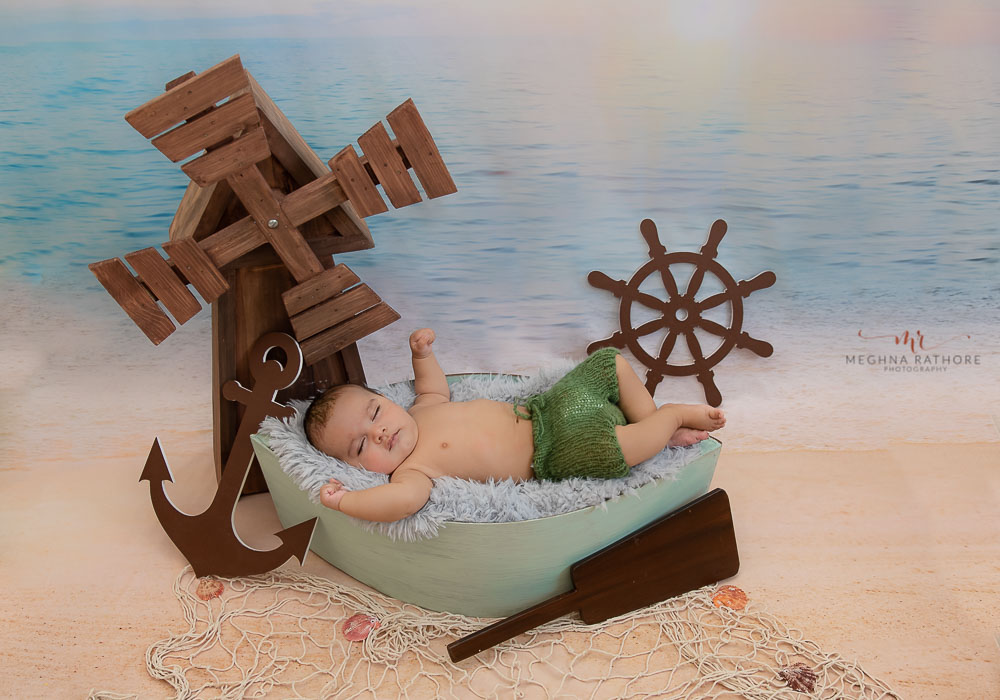 meghna rathore photography baby photo shoot baby lying in a small boat with beach background