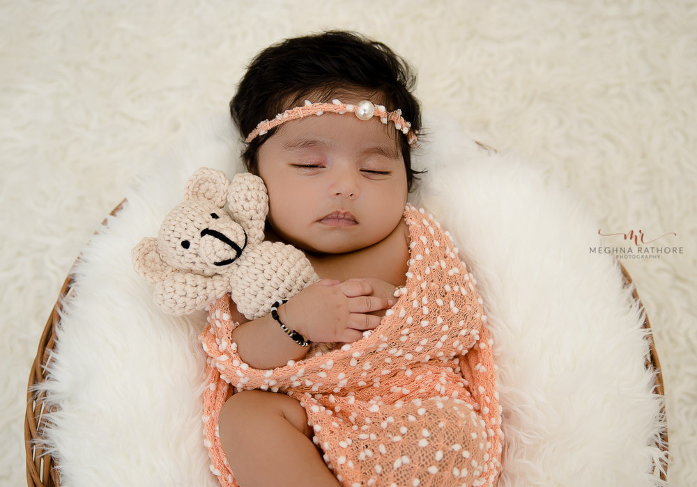 meghna rathore photography newboprn photo shoot baby lying in a basket with teddy in his hand and sleeping on white fur