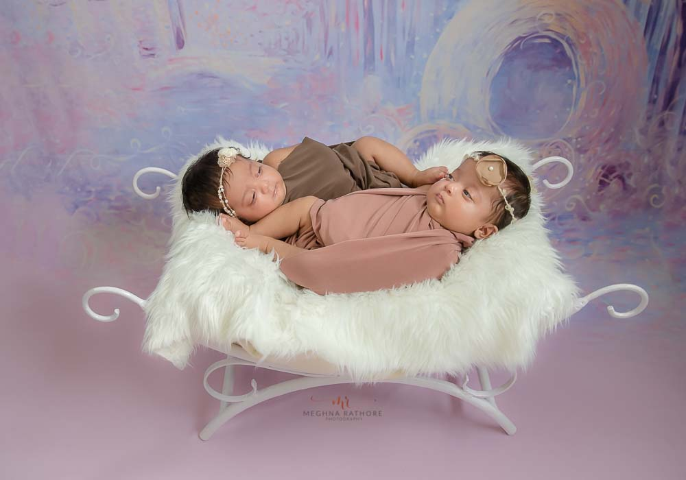 meghna rathore photography twin photo shoot both babies lying on a curved bed