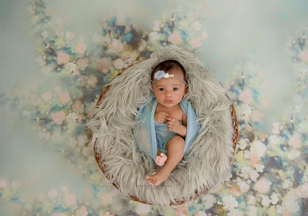 meghna rathore photography baby lying in a basket on grey fur delhi photo shoot
