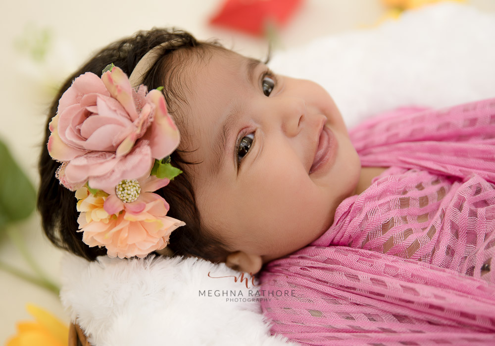 meghna rathore photography baby smiling and wrapped in cloth and cute headband
