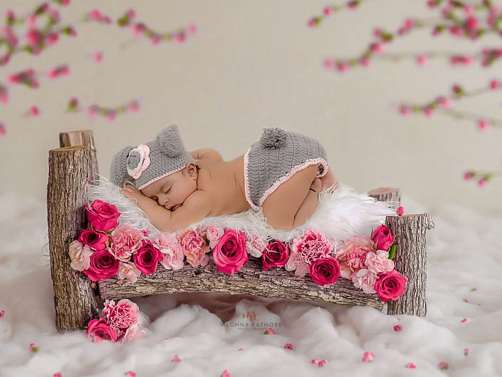 delhi professional baby photoshoot baby lying on a wooden log bed with white fur meghna rathore photography