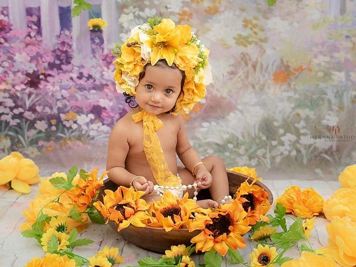 delhi gurgaon professional kid photoshoot kid sitting in a basket with floral decoration meghna rathore photography