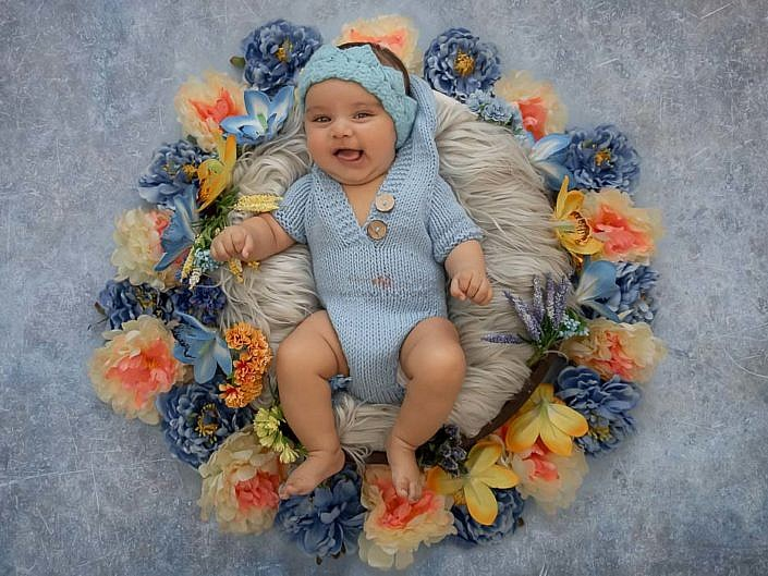 delhi gurgaon professional baby photographer baby in basket with floral decoration blue background meghna rathore photography