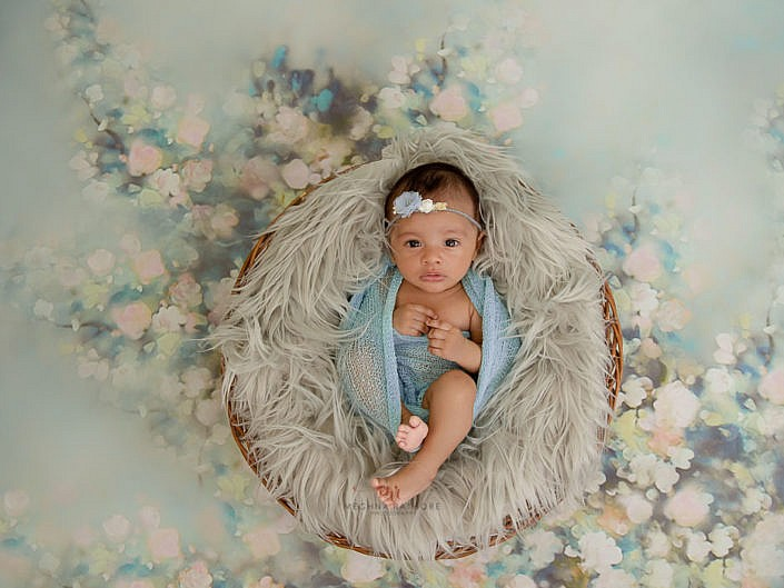 delhi gurgaon best newborn photgrapher baby sitting in a basket on fur meghna rathore photography