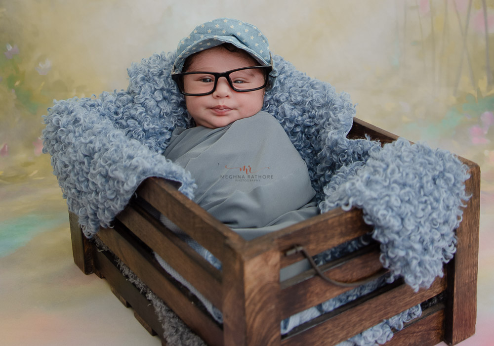 meghna rathore photography baby sitting in a box with cute glasses on and wrapped
