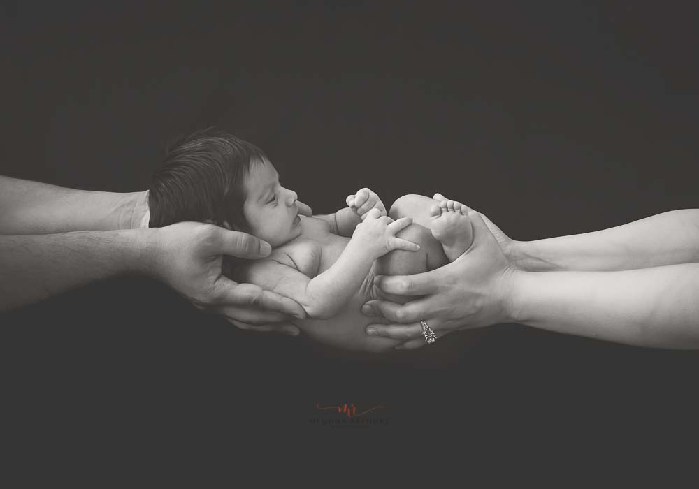 meghna rathore photography baby photo shoot mom and dad holding baby in hands