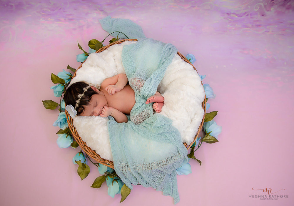 meghna rathore photography baby photo session of baby sleeping in a basket on white fur with flower decoration around and pink background