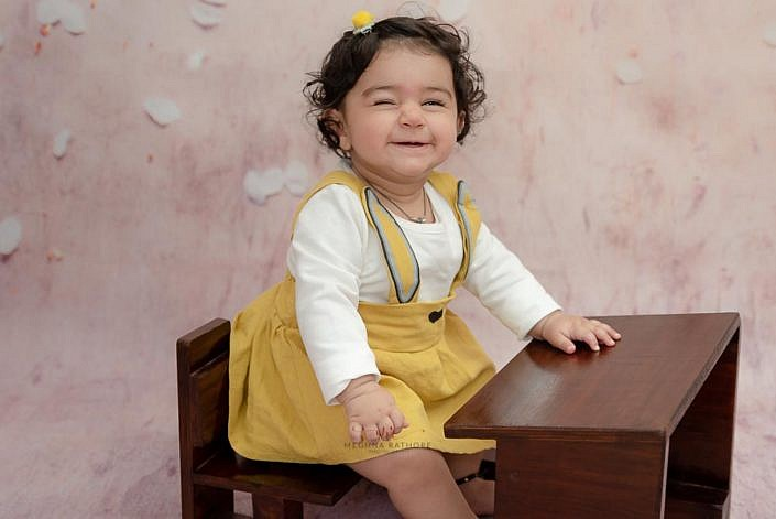 delhi kid photo shoot kid sitting on study bench and smiling meghna rathore photography