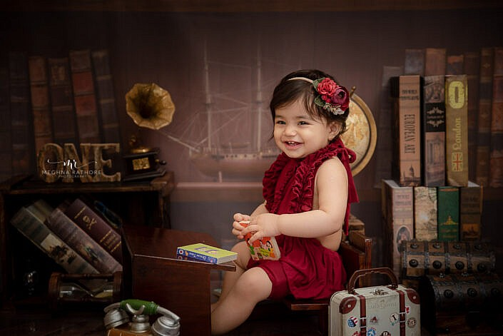baby girl sitter pose small books posing professional photo shoot Meghna Rathore Photography