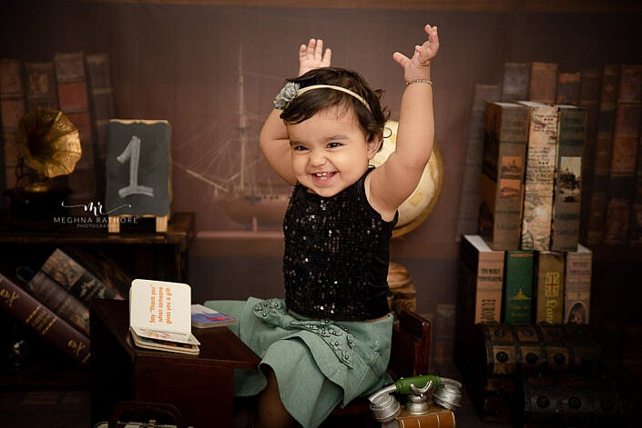 baby girl smiling poses small book study backdrop professional photo shoot Meghna Rathore Photography