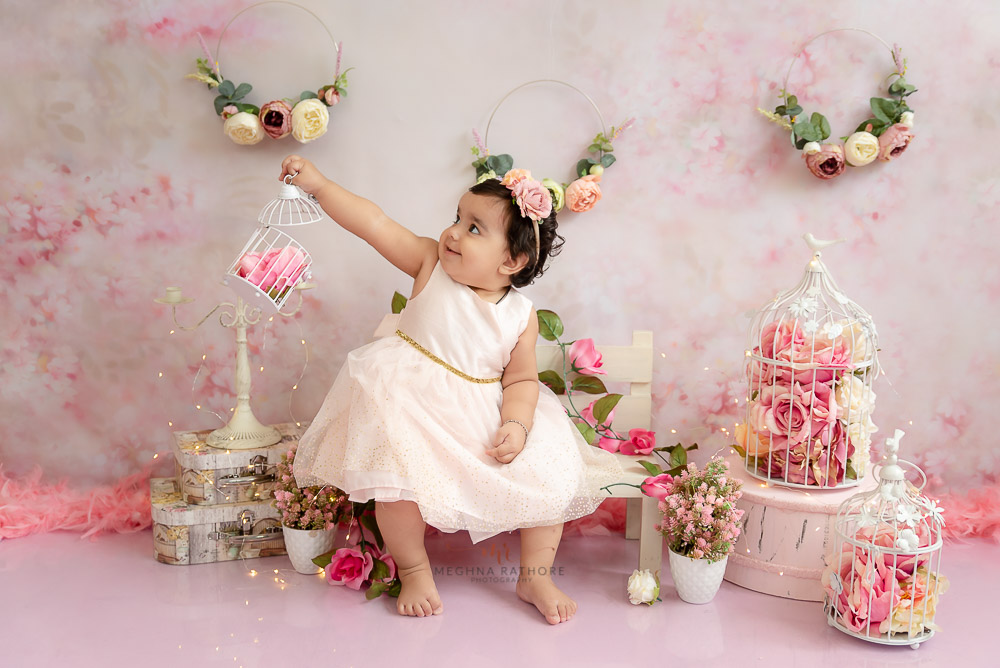 baby girl sitter photo shoot sitting on a white bench pink background delhi Meghna Rathore Photography