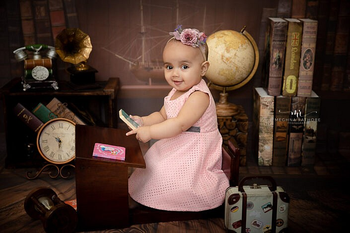 baby girl in pink dress sitting on a study desk brown backdrop professional photo shoot Meghna Rathore photography