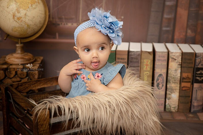 Baby in blue dress in wooden prop with study backdrop Meghna Rathore Photography baby photo shoot