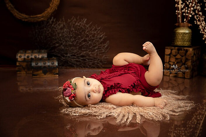 baby girl in red dress poses with floral head band dark brown backdrop props Meghna Rathore Photography