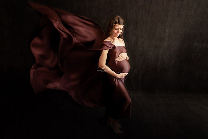 pregnant lady brown dress holding belly black backdrop Meghna Rathore Photography Delhi