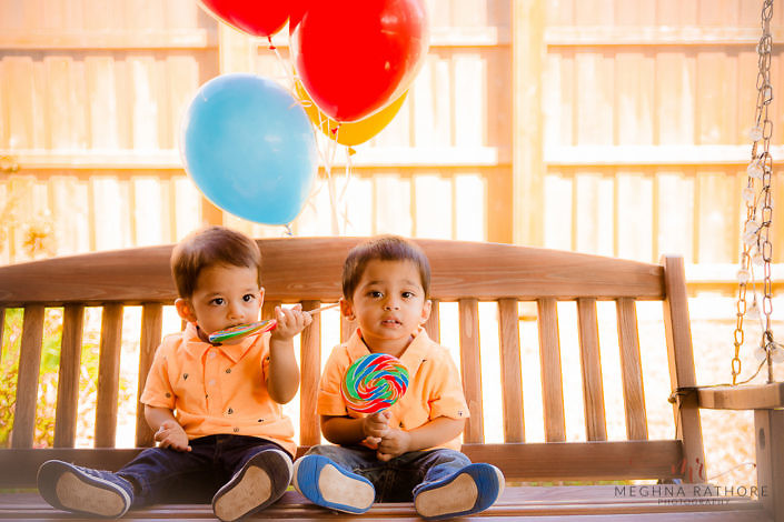 kid twins sitting on a swing and holding balloons - delhi professional kid photographer