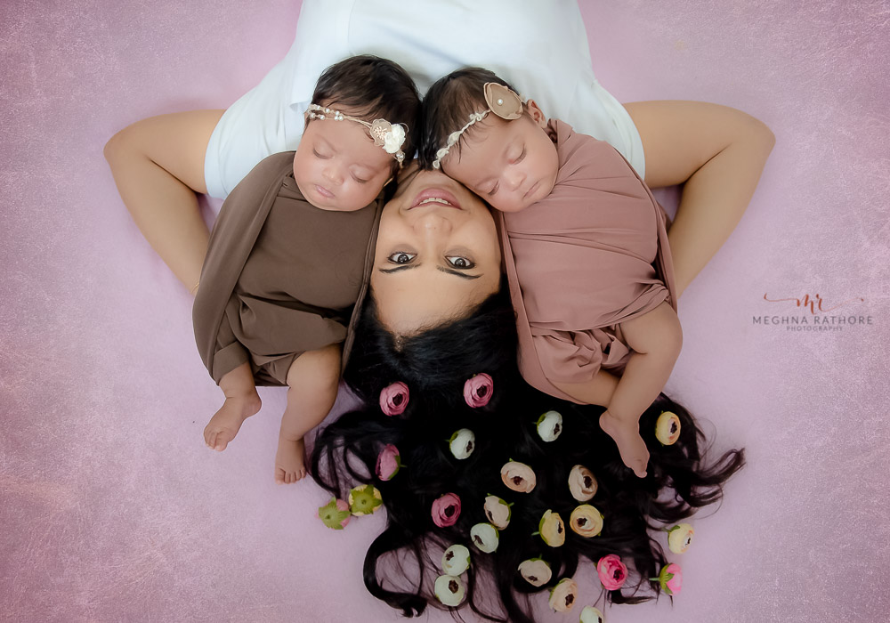 meghna rathore photography twin photo shoot delhi mom and both babies lying on floor with flower decoration