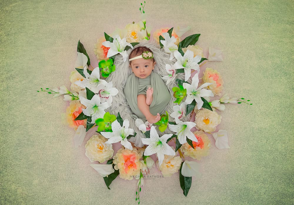 meghna rathore photography baby photo shoot baby in a basket with white and orange flower decoration and green backdrop