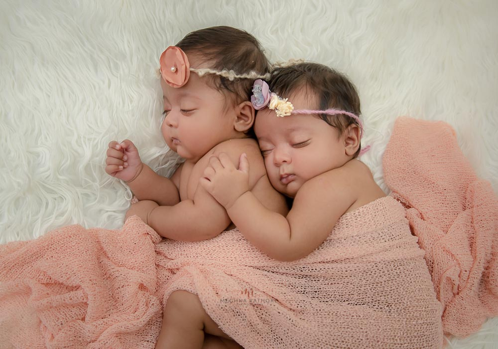 meghna rathore photography twin baby photo shoot delhi both babies hugging each other and sleeping on a white fur