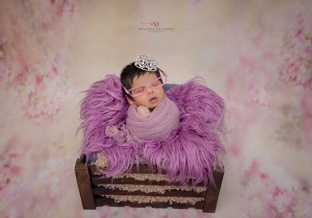 meghna rathore photography newborn baby photo shoot of baby wrapped in purple wrap with matching glasses and sitting in a box