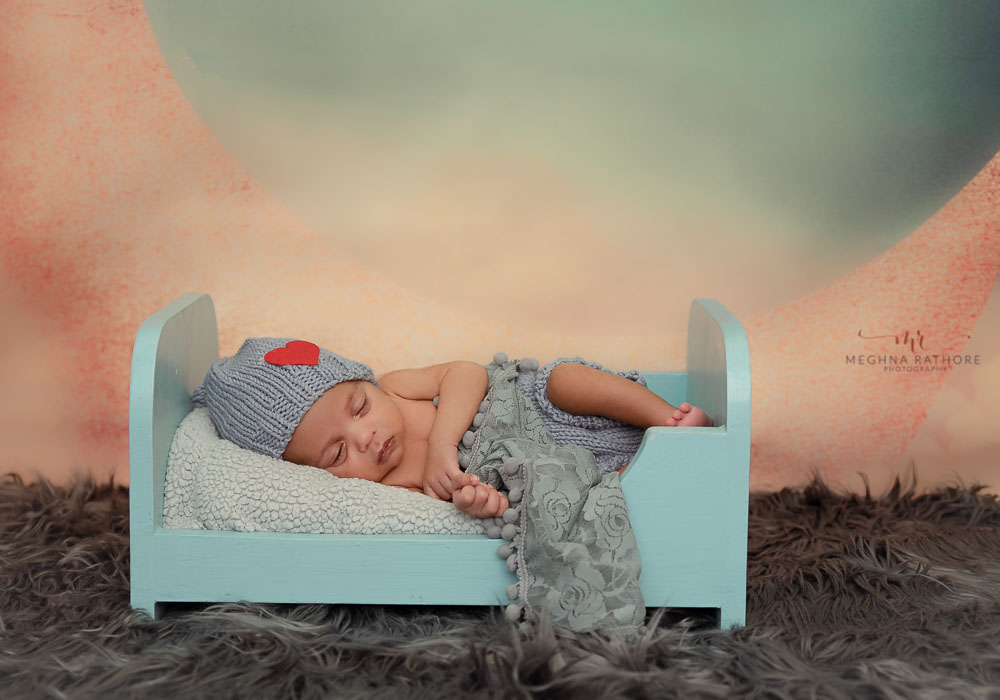 meghna rathore photography newborn baby sleeping on blue bed on soft fur baby photo shoot delhi