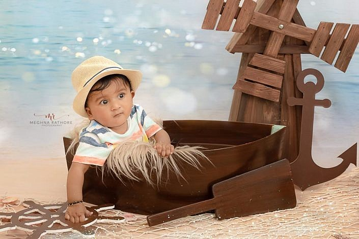 professional kid photo shoot kid sitting in small boat with beach backdrop meghna rathore photography
