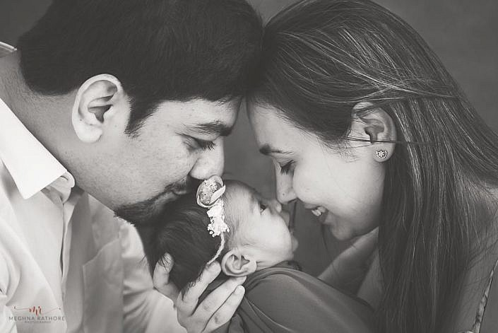 newborn in the arms of mom and dad who are kissing baby in black and white share delhi meghna rathore photography