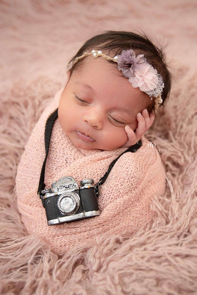 professional newborn photo shoot baby in potato sack with mini camera around his neck meghna rathore photography