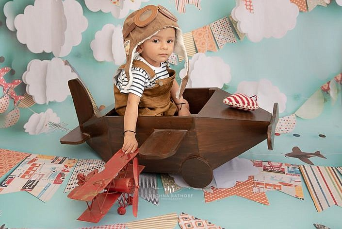 Meghna Rathore Photography, plane wooden prop, baby posing, red plane