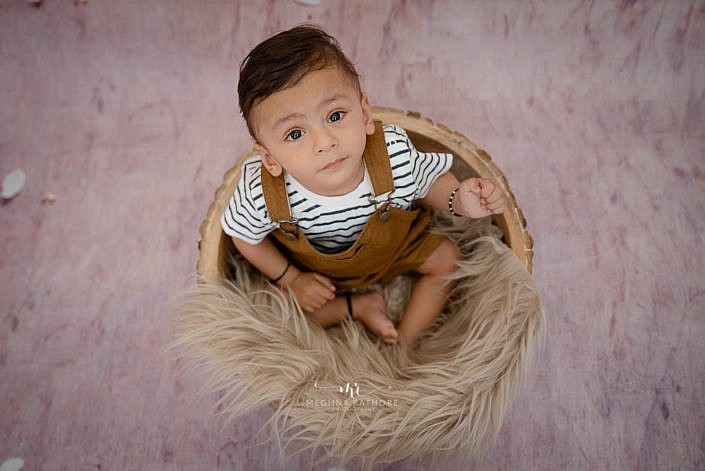 Meghna Rathore Photography, wooden bowl prop, toddler photoshoot, sitters photography, brown fur, baby smiling, indoor photography, studio