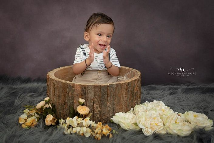 Meghna Rathore Photography, kid clapping, brown wooden prop, white flowers