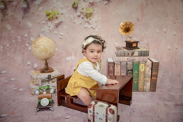 delhi kid professional photo session kid sitting on a bench with books around meghna rathore photography