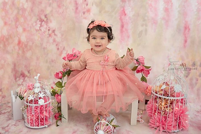 delhi kid photo shoot kid sitting on bench with flower around and matching pink bakdrop meghna rathore photography