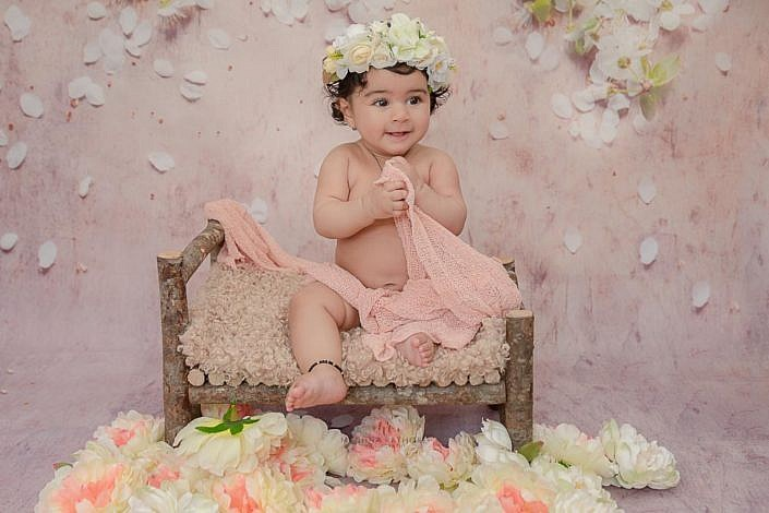 delhi kid photo shoot girl kid sitting on a wooden log bench with flower decoration around meghna rathore photography