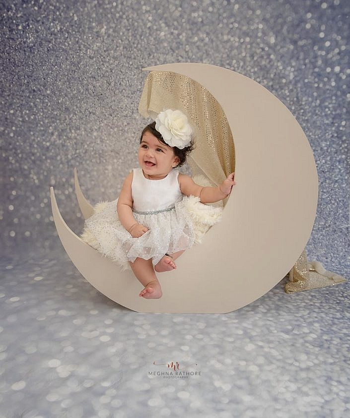 delhi kid photo shoot girl kid sitting on a white moon prop with sparkle background meghna rathore photography