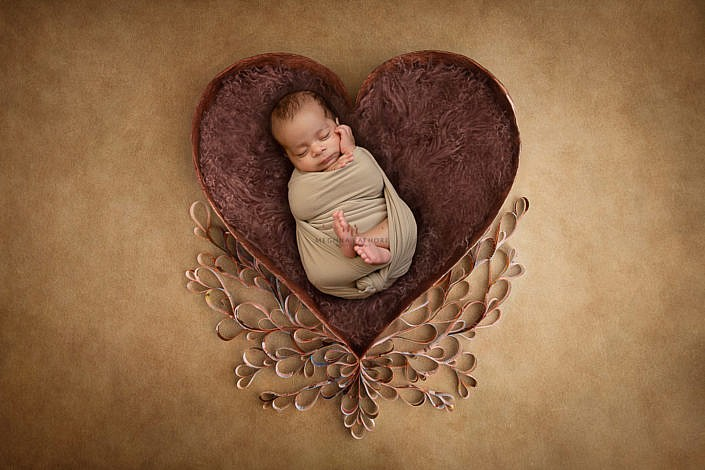 newborn photoshoot lying in heart bowl with prop decoration brown backdrop meghna rathore photography