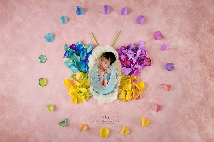 newborn photoshoot by professional photographer meghna rathore delhi gurgaon baby lying with a butterfly decoration using leave pink backdrop
