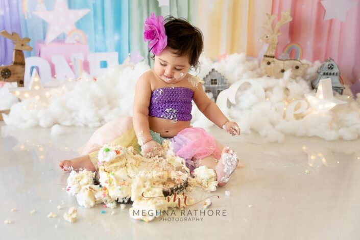 1 year old cute baby girl cake smash indoor professional photoshoot looking at cake in beautiful outfit at meghna rathore photography in delhi gurgaon