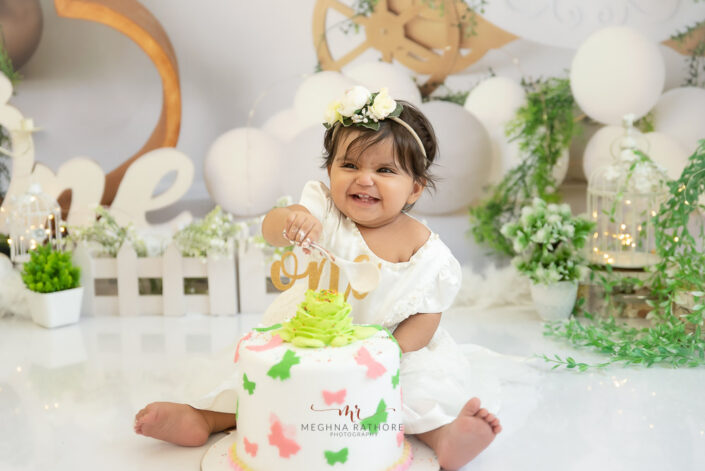 1 year old cute baby girl cake smash indoor professional photoshoot smiling and posing with a spoon in her hand at meghna rathore photography in delhi gurgaon