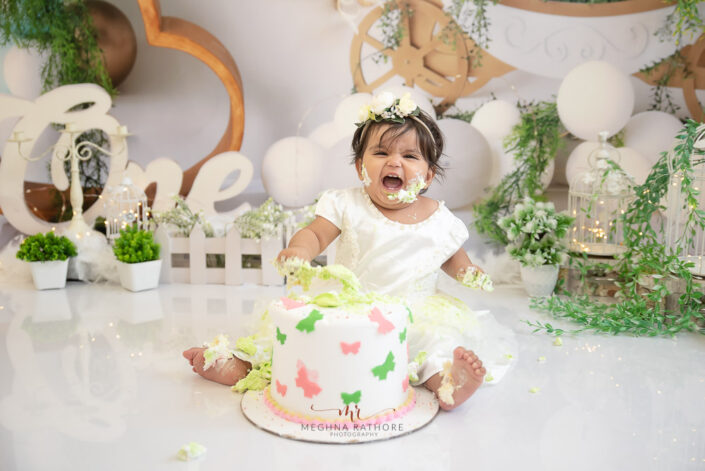 1 year old cute baby girl cake smash indoor professional photoshoot smiling at meghna rathore photography in delhi gurgaon