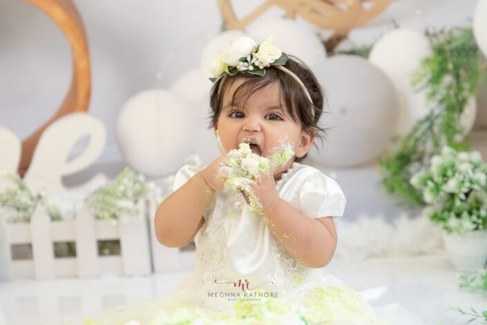 1 year old adorable baby girl cake smash indoor professional photoshoot posing into camera at meghna rathore photography in delhi gurgaon