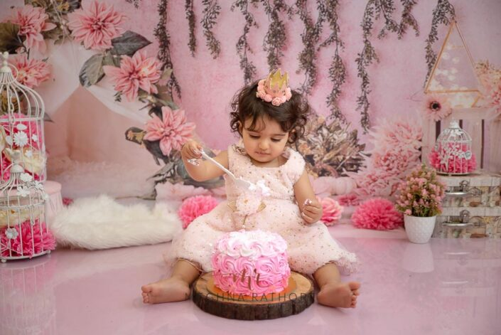 1 year old cute girl photo shoot poses smiling brightly while smashing the cake for meghna rathore photography in delhi gurgaon