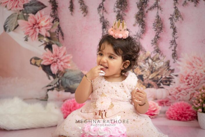 1 year old cute girl photo shoot poses biting her fingers for meghna rathore photography in delhi gurgaon