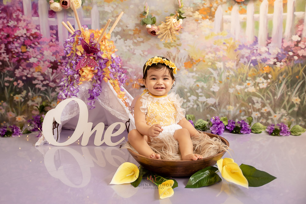 baby girl yellow dress one year posing in bucket tent prop backdrop Meghna Rathore Photography